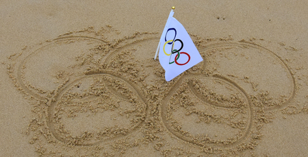 olympic rings: Sydney, Australia - Jul 31, 2016 Olympic rings drawn in the sand and olympic flag in the center. Summer Olympic Games