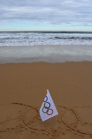 olympic rings: Sydney, Australia - Jul 31, 2016 Olympic rings drawn in the sand with an Olympic flag. Summer Olympic Games. Editorial