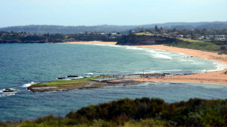 Mona Vale rock pools in the distant panoramic view from the elevated lookout During low tide surfing waves and sandy beach, sydney australia Northern Beaches Stock Photo