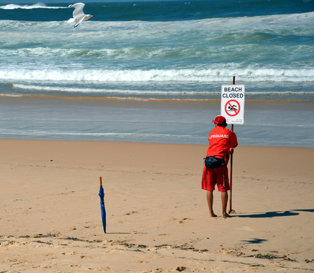 violation: The sign reads beach is closed. No swimming flags on the beach before  after storm.