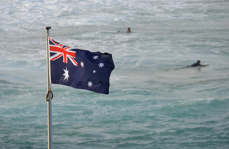 Australian flag waving in the wind. Surfers on the beach in the background.