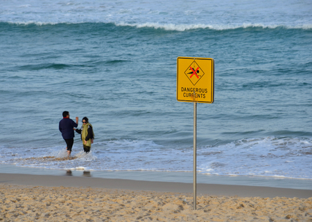 currents: Sydney, Australia - Jun 9, 2013. A sign reads Dangerous currents. Swimming is forbidden.