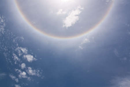 Circles halo in the blue cloudy sky around of the sun  photo