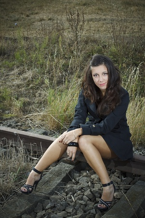 flirtatious: A beautiful young woman with long brown hair wearing a black jacket and black sandals is sitting on the rail, looking sexy Stock Photo