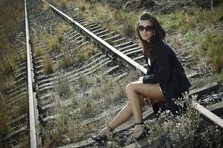A beautiful young woman with long brown hair wearing a black jacket, sunglasses and black sandals is sitting on the rail, looking sexy Stock Photo