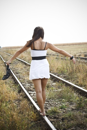 wind blown hair: An attractive young woman with long brown hair blown by the wind, wearing a white mini dress and holding a black high-heel sandal in her left hand is walking bare feet on the railway Stock Photo