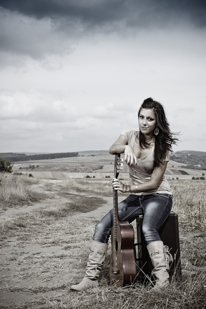 cowgirl boots: A beautiful young woman with long brown hair blown by the wind, wearing boots, jeans and a top, is sitting on a suitcase, and leaning on her guitar,countryside in the background