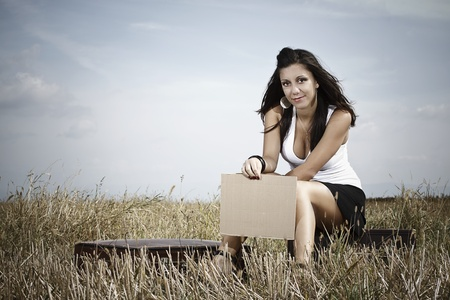 A smiling beautiful young woman with long brown hair,wearing a white top and black mini skirt,is sitting in the medow, holding a blank sheet in her hand,her suitcase is next to her, h
