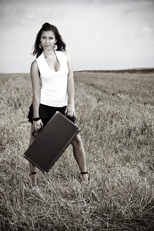 A smiling beautiful young woman with long brown hair,wearing a white top and black mini skirt is standing in the medow, holding a suitcase in her hands Stock Photo