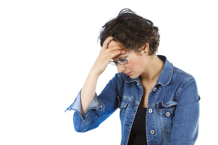 An attractive young woman with glasses, short brown hair, wearing black top and jeans is having a headache, or some problems are depressing her, she is touching her forehead with her fingers - isolated on white