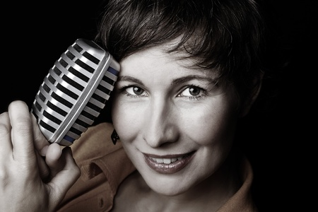 studio b: A portrait of a smiling attractive young woman with short brown hair, holding a microphone in her hand, looking into the cam - black background