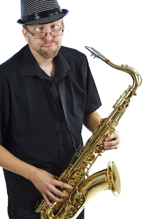 A young man with glasses wearing a hat and black shirt and holding a saxophone in his hands, making funny grimace - isolated on white
