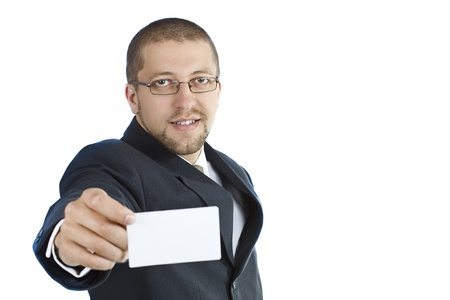 A young smiling businessman in suit wearing glasses is holding a blank business card in his right hand - isolated on white