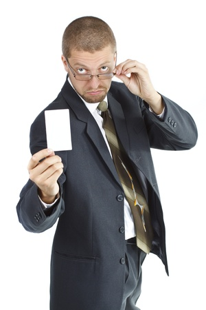 A young businessman wearing suit and tie is holding a blank card in his right hand, touching his glasses with his left hand and looking from behind his glasses - isolated on white Stock Photo