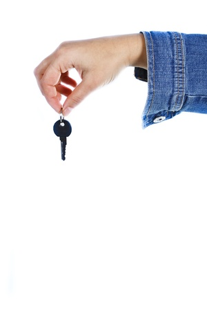 Close-up of a female hand holding a key between her forefinger and thumb - isolated on white photo