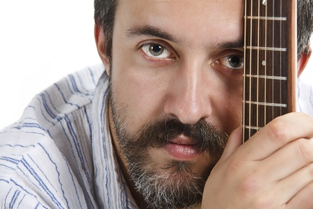 A young man with moustache and beard is looking from behind a guitars fretboard photo