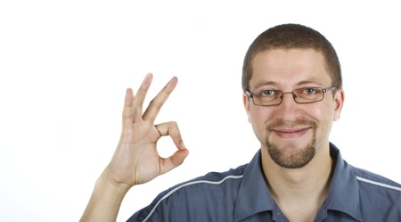rightly: A young smiling man with glasses wearing blue shirt is showing the ok sign with his right hand, looking into the camera Stock Photo