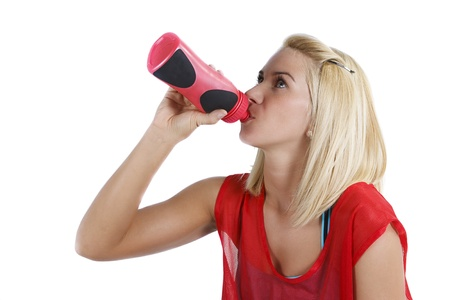 An attractive young sportswoman with blonde hair, in red sportswear, drinking from a red bottle - isolated on white