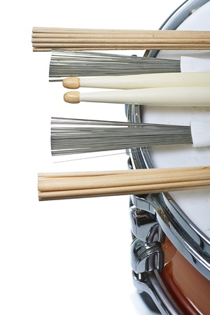 unplugged: Drumsticks,brushes and unplugged sticks resting on a cherry sunburst coloured snare drum, shown only a part of its side and top with the metal rim- isolated on white Stock Photo