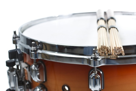 Close-up of unplugged sticks resting on a cherry sunburst coloured snare drum, shown only a part of its side and top with the metal rim - isolated on white
