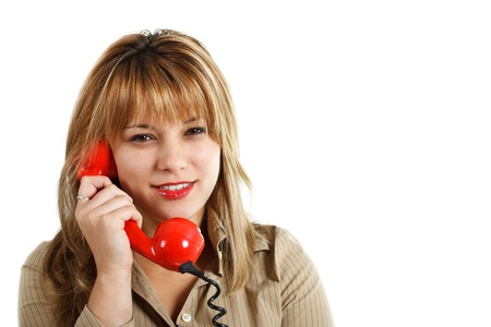 An attractive young woman with long blond hair is smiling and holding a red retro telephone, looking into the camera - isolated on white Stock Photo