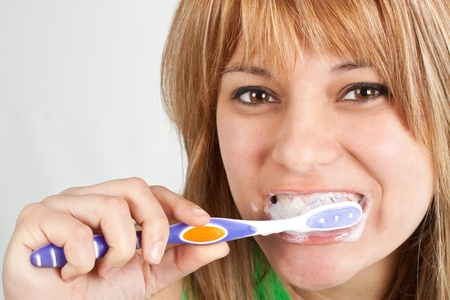 A young girl with long blond hair, brown eyes, is brushing her teeth with a purple and white toothbrush and with foaming toothpaste - isolated on white Stock Photo