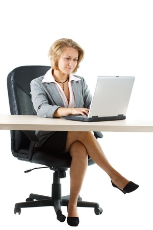 skirt suit: A young blond attractive businesswoman in skirt sitting at her desk and looking attentively at her laptop, full figure with legs is shown - isolated on white