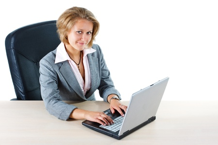 A young blond attractive businesswoman sitting at her desk smiling, with laptop, and looking into the camera - isolated on white Stock Photo - 11712051