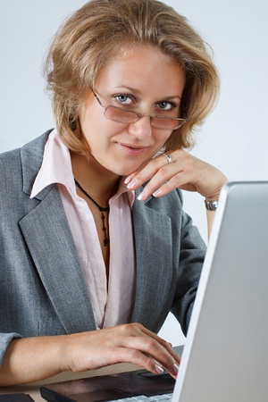 Portrait of an attractive young blond businesswoman with glasses is working with her laptop and smilinginto the camera Stock Photo - 11712068
