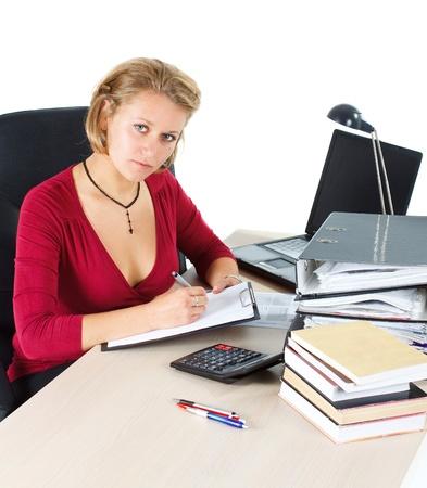 looking into camera: Un attraente giovane imprenditrice bionda che indossa un top sexy rossa, scrivendo sul suo taccuino, lavorando alla sua scrivania piena di libri, una calcolatrice, penne, il suo computer portatile, una lampada, sta guardando la telecamera - isolato su bianco