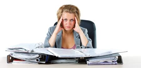 Une jeune femme d'affaires blonde assise derrière son bureau avec des dossiers, la recherche surchargés de travail, stressé, fatigué, en regardant dans la caméra - isolé sur blanc