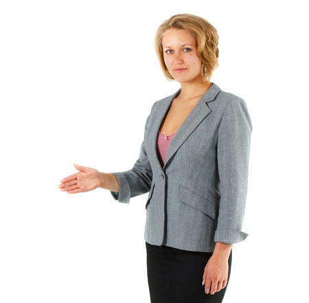 A young attractive blond businesswoman in suit is standing, giving hand for handshake, looking into camera - isolated on white photo