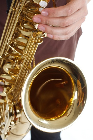 Close-up of a man wearing brown shirt is playing the saxophone, only the instrument and fingers are shown - isolated on white