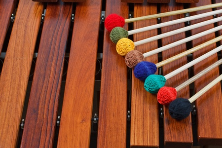 Close-up of coloured mallets on a wooden marimba