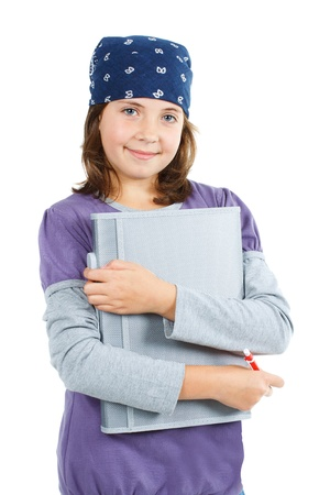 A cute 9-year-old girl with a blue scarf on her head, wearing purple and grey top, holding a grey notebook and a pen, smiling into the camera - isolated on white