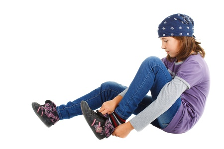 A cute 9-year-old girl with a blue scarf on her head, wearing purple and grey top and jeans, sitting and putting her shoe on - isolated on white photo