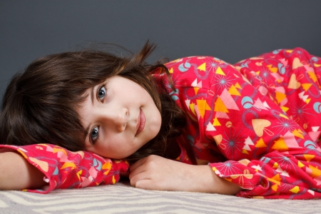 A cute 9-year-old girl lying in colourful pyjamas, looking into camera - grey background photo
