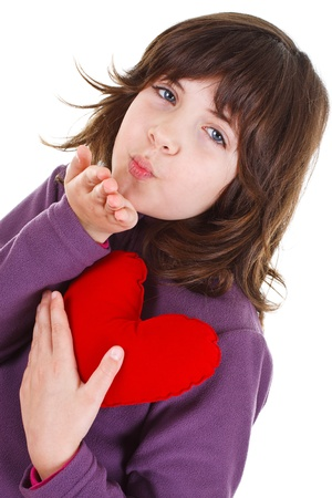 A cute 9-year-old girl with long brown hair and blue eyes is blowing kiss, holding a red heart in her hand - isolated on white