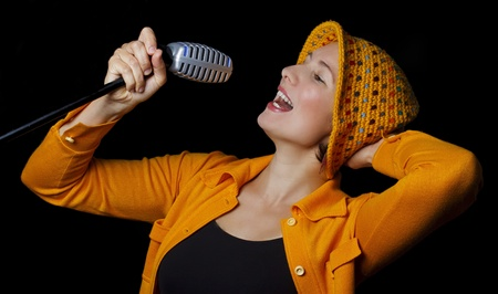 An attractive young woman wearing a yellow cap, yellow sweater, black top, holding a microphone in her right hand, singing with eyes closed, her head bent backword a bit, touching her head withe her left hand - isolated on black