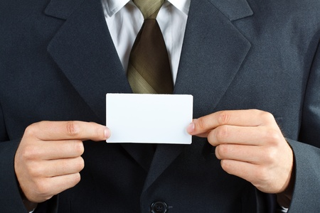 both: Close-up of a businessman with suit and tie, holding a blank card with both hands, with forefingers and thumbs