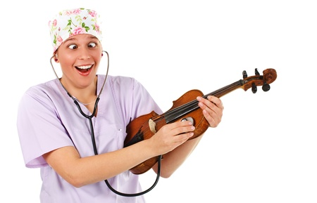 violin making: An attractive young female doctor wearing a light purple uniform, a coloured cap, making a funny grimace, examining a violin with a stethoscope - isolated on white