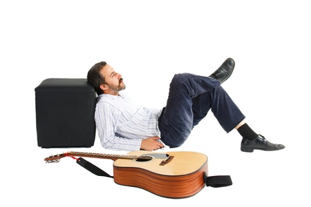 A young man with moustache and beard, is lying on the floor with eyes closed, leaning to a balck stool, crossing his legs, and a guitar is lying next to him in the front - isolated on white