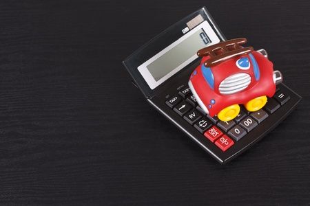 A red toy car, a toy fire engine is on a calculator - isolated on black photo