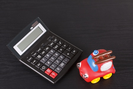 A red toy car, a toy fire engine is next to a calculator - isolated on black Stock Photo - 11711994