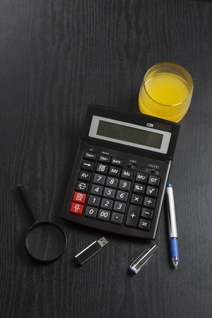 A calculator is on a black desk surrounded by a magnifying lens, a flesh drive, a pen and a glass of orange juice photo