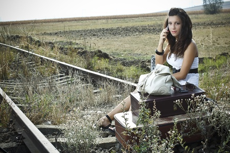 An attractive young woman with long brown hair is sitting on the rail road with old-fashioned suitcases in the front,she is waiting an making a call with her mobile phone