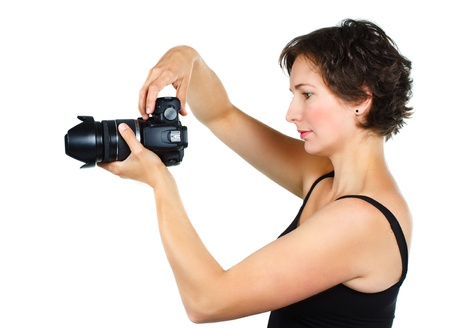 An attractive young woman with short brown hair, in a black top,with shoulders and arms, holding a camera, showing her left side - isolated on white
