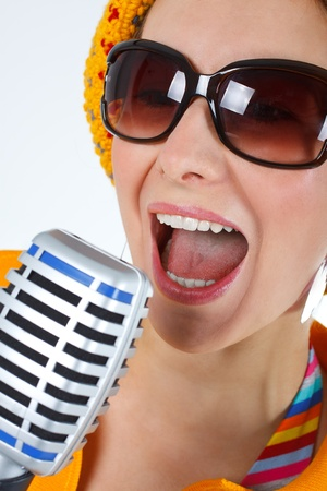 kareoke: A young woman with sunglasses, yellow hat, colourful clothes, mouth wide open, singing into the microphone - isolated on white Stock Photo