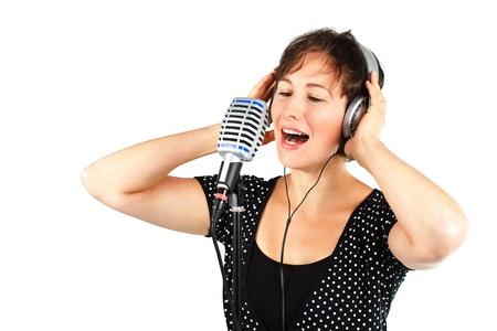 Portrait of a young attractive woman in a balck top with white dots, short brown hair, eyes closed, singing into the microphone, holding headset with both hands - isolated on white