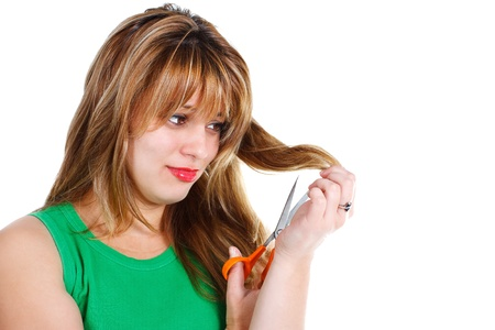 An attractive young blond woman cutting her hair with scissors - isolated on white